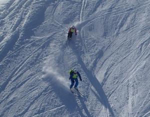 Begeleider en deelnemer recht van boven gezien vanuit een skilift