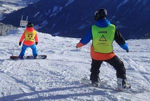Snowboarden, deelnemer voorop, begeleider volgt en geeft aanwijzingen